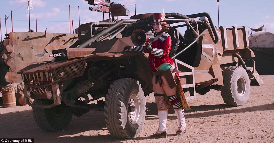 A festival goer poses next to one of the Mad Max-style vehicles during the Wasteland Weekend festival in the Mojave desert