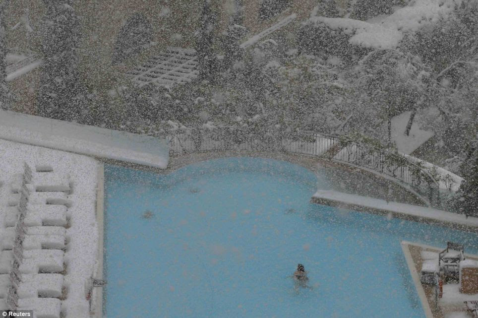 Cold comfort: A woman swims in the pool at the David Citadel Hotel during a snow storm in Jerusalem today