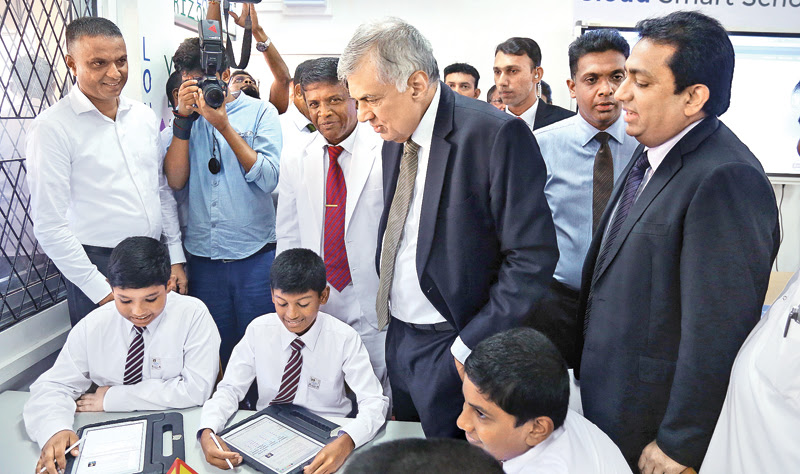 Prime Minister Ranil Wickremesinghe who went on an observational tour of the 'smart class' introduced at the Sri Jayawardenepura Maha Vidyalaya, Kotte yesterday is seen talking to the students. Picture by Nirosh Batapola.