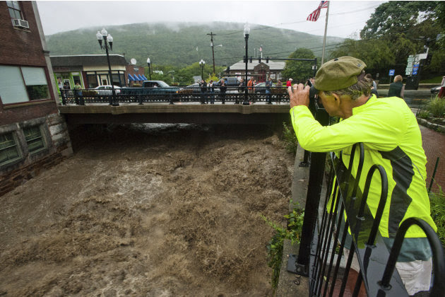 Mel Martin joins a crowd watching the raging Whetstone Brook surge over the falls in downtown Brattleboro, Vt. on Sunday, Aug. 28, 2011. The remnants of Hurricane Irene dumped torrential rains on Verm