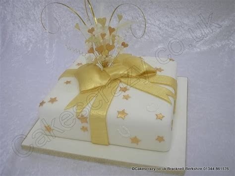 Square ivory coloured celebration cake covered in gold