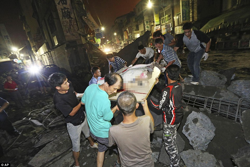 Disaster zone: The body of a victim killed in the gas explosion from an underground leak is carried from the rubble in a main street in Kaohsiung