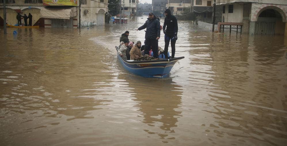 Palestinian policeman loyal to Hamas evacuates people from houses which flooded in northern Gaza