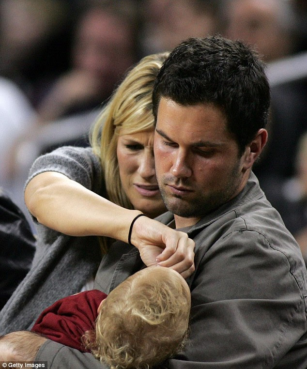 Former USC football quarterback Matt Leinart and Bryn Cameron attend to their son, Cole, during the Pac-10 Conference game between the UCLA Bruins and the USC Trojans at the Galen Center on February 17, 2008 in Los Angeles