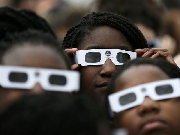 Crianças inglesas com óculos especiais tentam acompanhar o eclipse solar desta sexta-feira no Observatório Real de Greenwich, em Londres (Foto: Stefan Wermuth/Reuters)