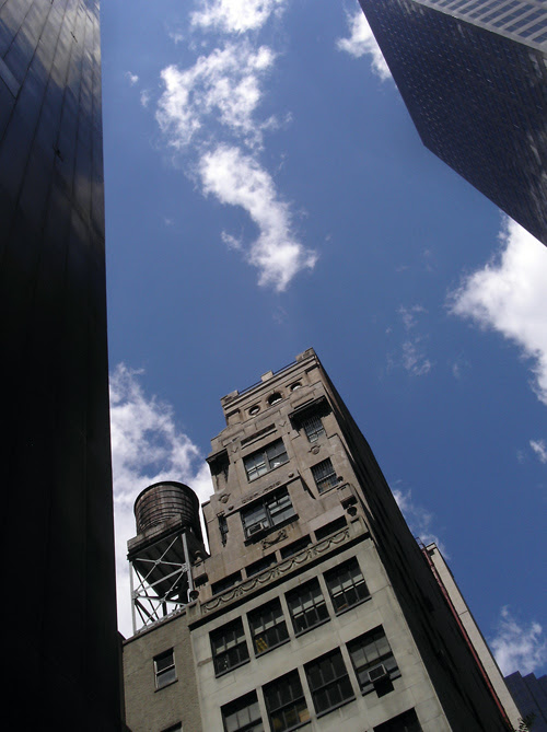 a water tower and clouds seen through midtown buildings, Manhattan, NYC