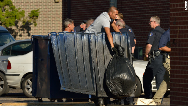 Agents search the trash container outside the suspect's apartment in Aurora.