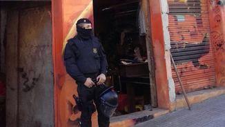Un agent vigila l'entrada del bloc okupa escorcollat