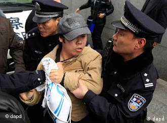 A man, center, is detained by police officers, near the planned protest site is located, in Shanghai, China, Sunday, Feb. 27, 2011. Large numbers of police, and use of new tactics like shrill whistles and street cleaners, are squelching any overt protests in China after calls for more peaceful gatherings modeled on recent popular democratic movements in the Middle East. (AP Photo/Eugene Hoshiko)