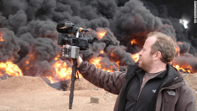 <br/>CNN senior photojournalist Neil Hallsworth films an oil fire in Homs, Syria.