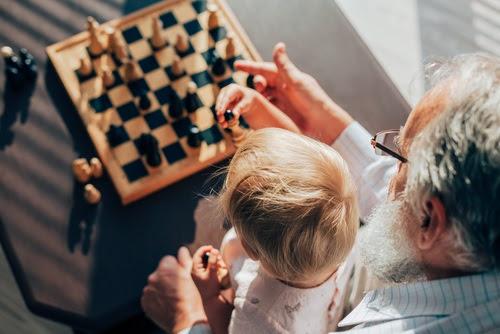 Un abuelo jugando con su nieto a la ajedrez