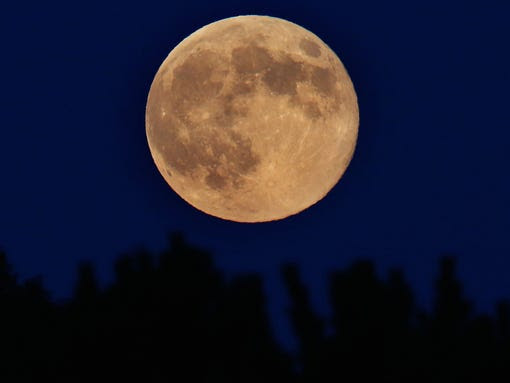 A supermoon rises through the trees   in Spencer, N.Y.,