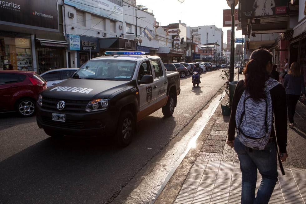 Un coche de la policía recorre una calle comercial de Martínez, en la periferia norte de Buenos Aires.