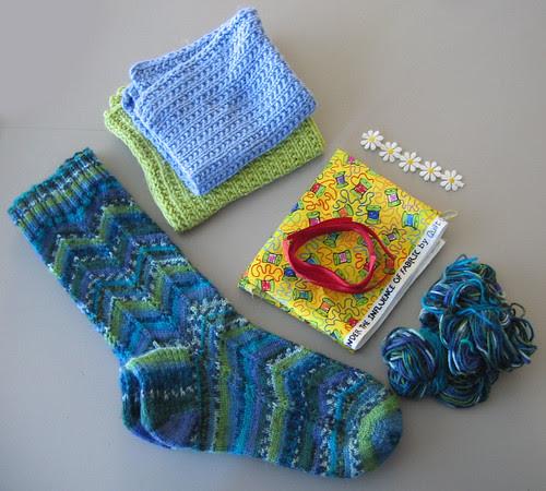 et par sokker, et par vaskekluter, et rødt bånd og et hvit blomsterbånd, og et bit stoff :: a pair of socks, a pair of washcloths, ribbons and trims, and a piece of fabric