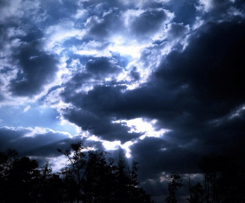 [Photo of sunshine behind dark clouds]