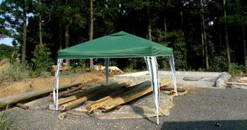 テントの下で丸太加工