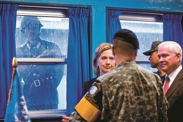 힐러리 클린턴이 로버트 게이츠 국방장관과 함께 판문점을 방문한 모습. 북한 군인이 창문 너머로 들여다보고 있다./김영사 제공, Photo by Cherie Cullen, DOD via Getty Images