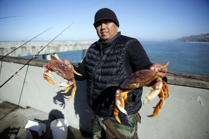Jimmy Narag holds two of the crabs he caught off Pacifica Municipal Pier in Pacifica, California, on Sunday, Feb. 21, 2016.