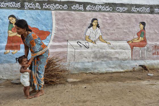 Una mujer y su hija frente a uno de las pinturas que en el pueblo de Pendlimanu se utilizan para educar a los vecinos sobre hábitos saludables.