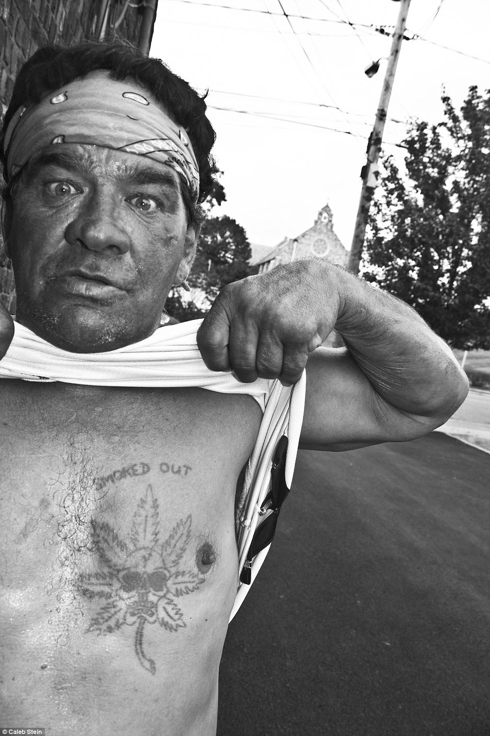 Striking new images show how some residents living just outside of New York City in Poughkeepsie are living below the poverty line as drugs and sex work run rampant in the city. Pictured above is a man named Artie showing off his 'smoked out' chest tattoo