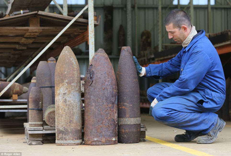 Cpl. Nico Sierens stands with a collection of rusting World War I shells discovered 100 years later in the former fields of battle