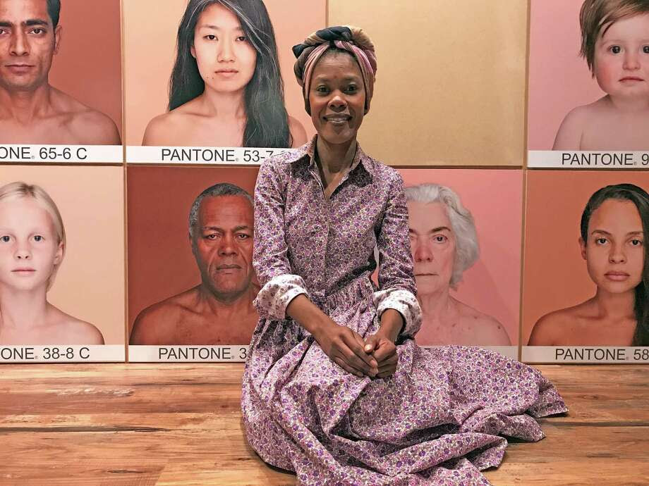 """Angelica Dass, a Brazilian artist who lives in Spain, poses at the entrance to her exhibition """"Humanae,"""" on view at the Health Museum through Sept. 5. Photo: Molly Glentzer, Houston Chronicle"""