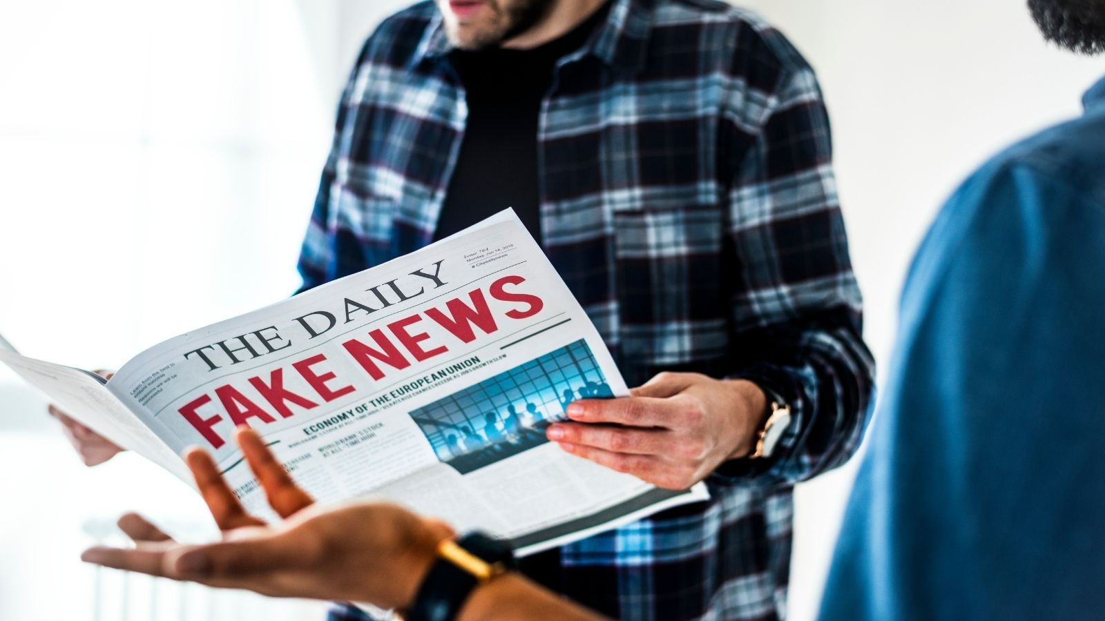 A man holds fake news newspaper to conceptualize controversy