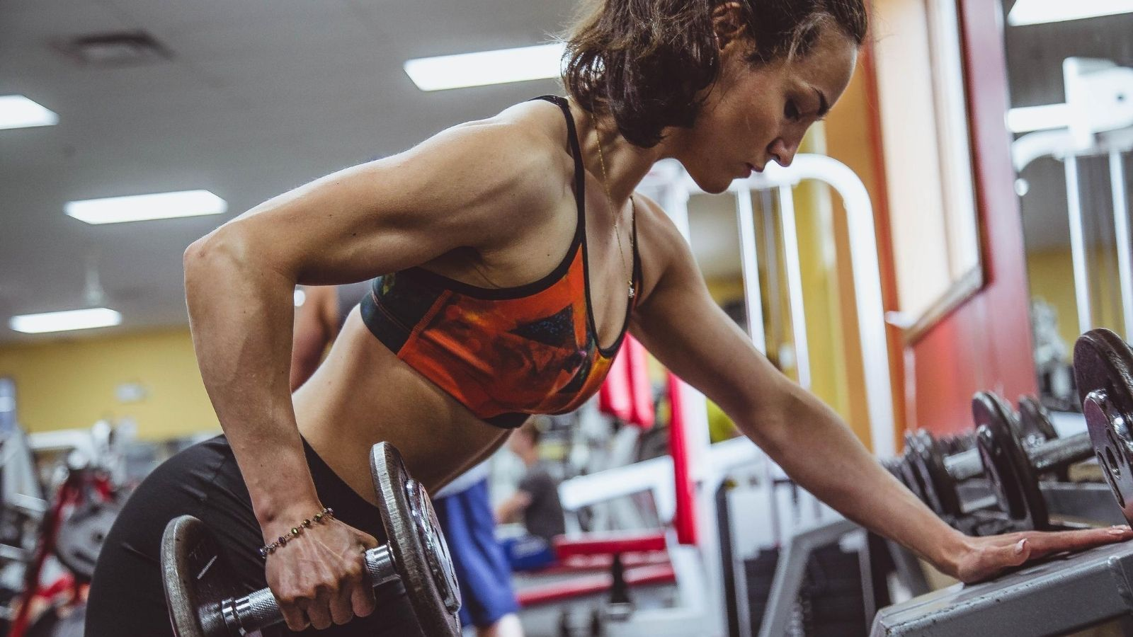 Focused woman lifting heavy weights at the gym
