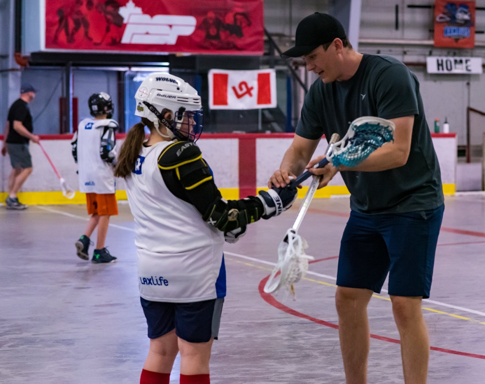 New England Black Wolves star forward Steph LeBlanc shows a Laxlife camper how to properly hold the stick