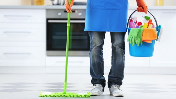 man holding a bucket of cleaning supplies and a dust mop