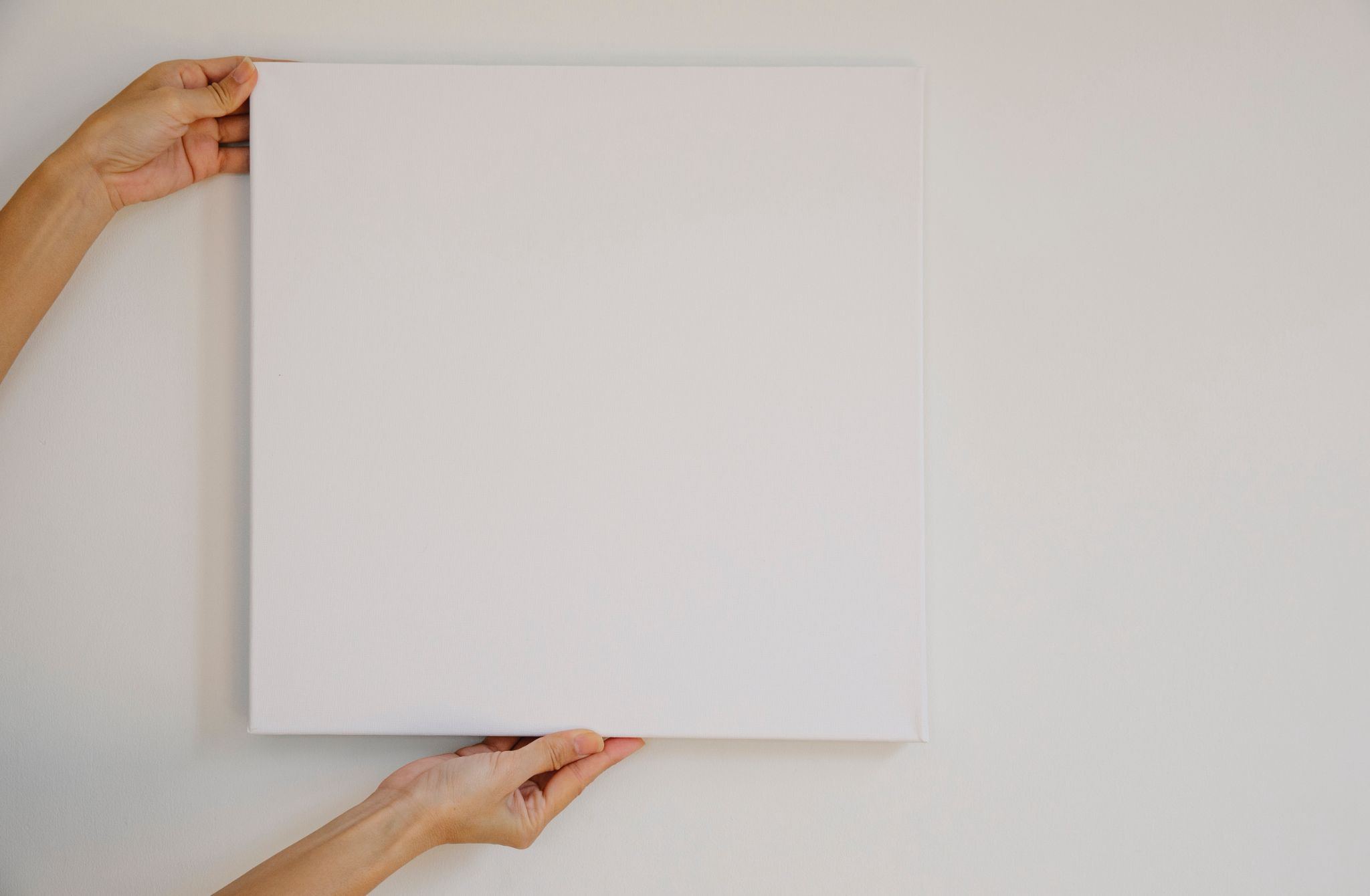 blank canvas being held against a white wall