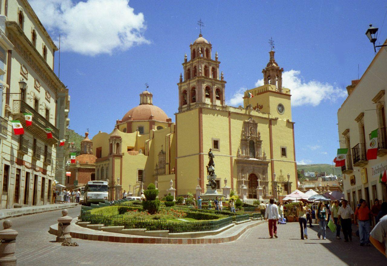 Un grupo de personas caminando en la calle al lado de una iglesia  Descripción generada automáticamente
