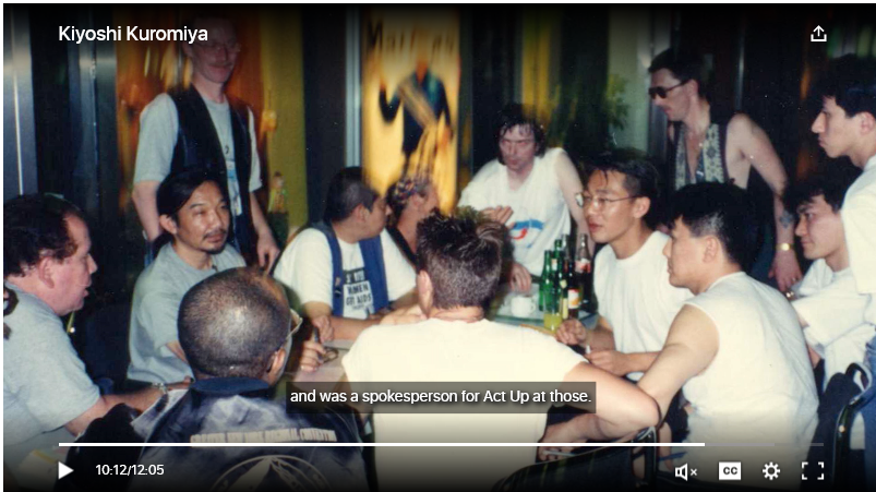A video still showing a photo of Kiyoshi Kuromiya and other queer Asian activists at a meeting.