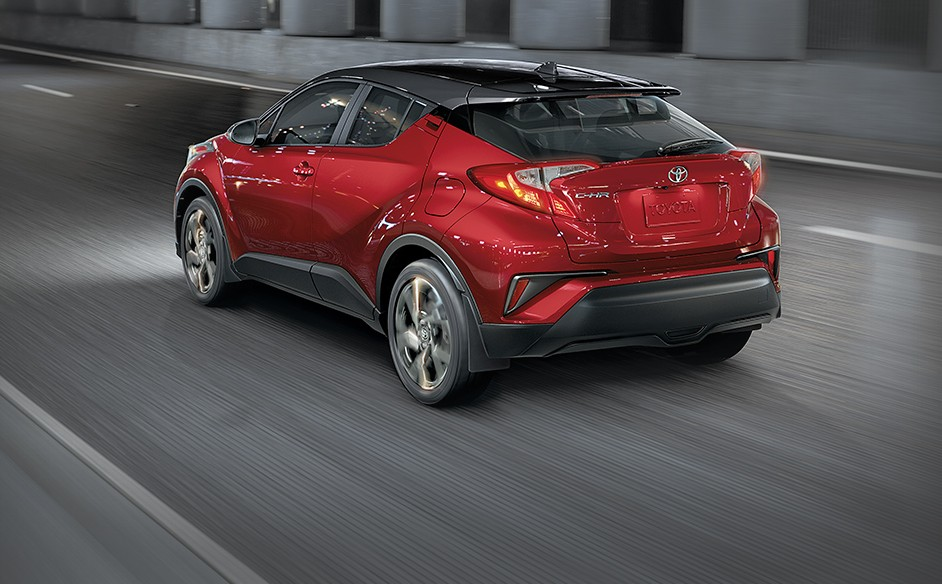 A red Toyota C-HR drives through the streets of Whitehorse, YK