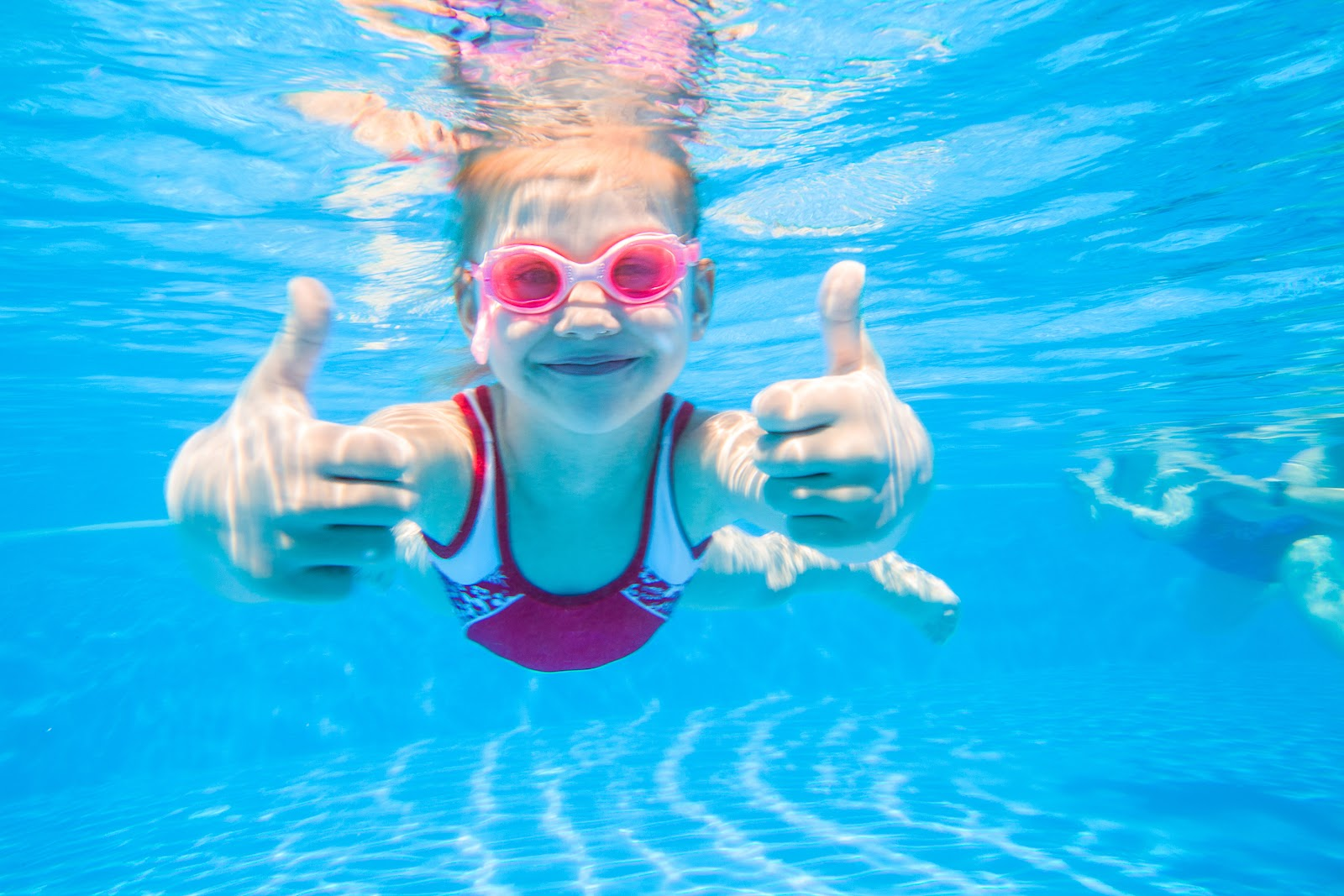 a young girl wearing pink googles giving two thumbs up underwater in a swimming pool