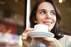Young Businesswoman Having a Coffee Break. No tinnitus symptoms present.