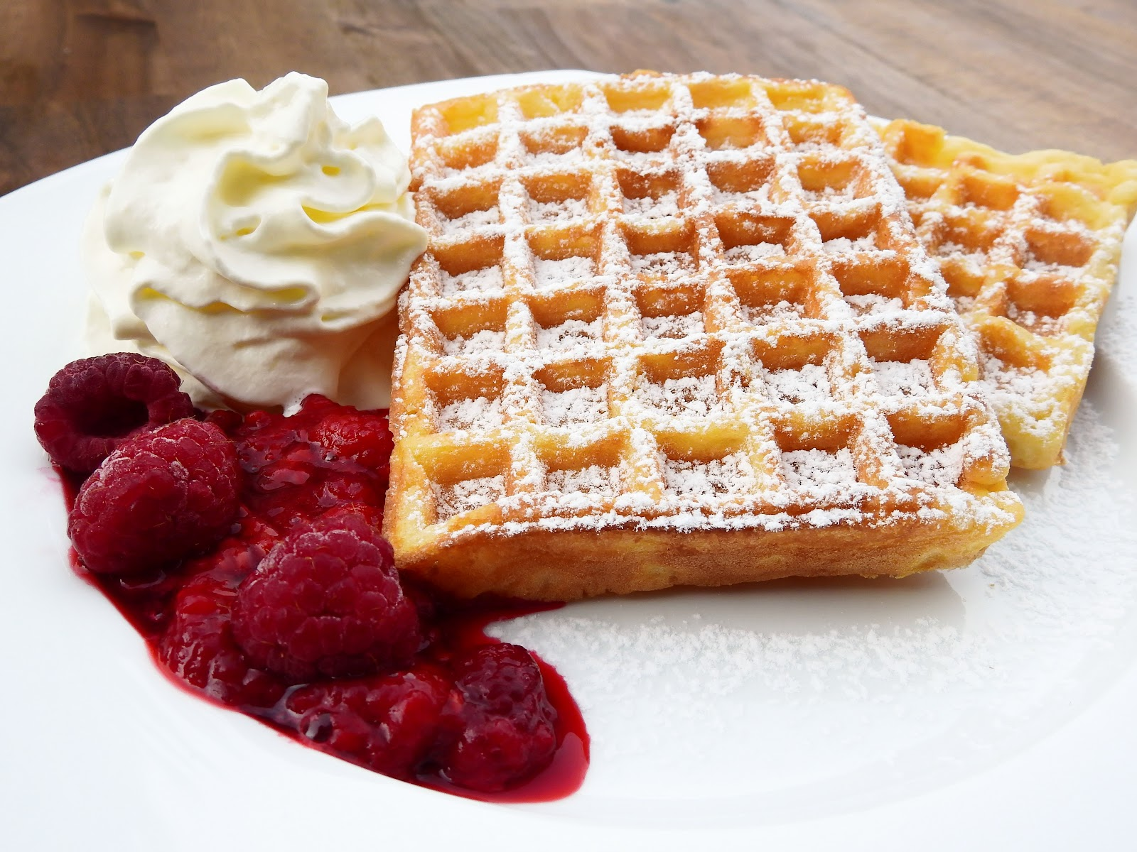 Waffle with raspberries and whip cream on a plate.