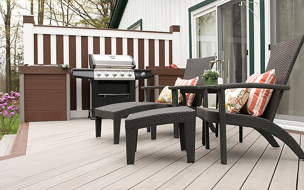 two chairs and grill on wooden deck