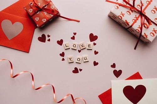 """Napis """" Ilove You"""" pośród świątecznych dekoracji i walentynkowych upominków."""