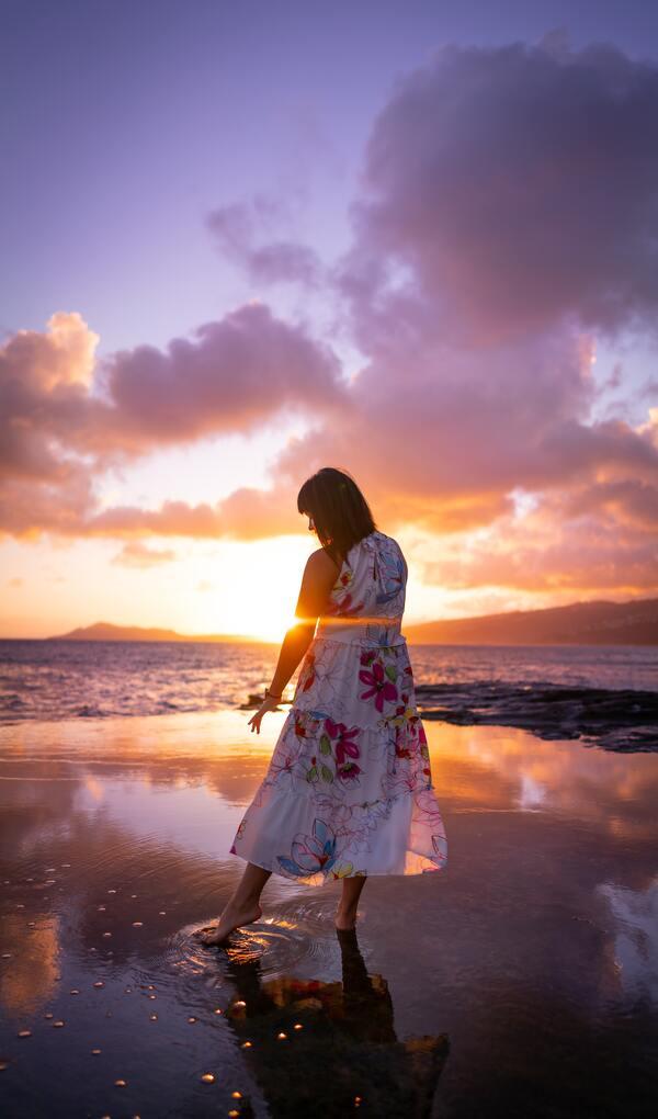 Foto de uma mulher na praia com os pés na água olhando para o pôr-do-sol