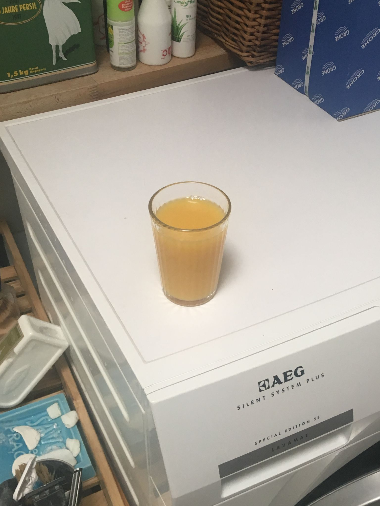 A glass of orange juice on a washing machine.  There is clutter around and on the machine.