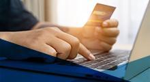 laptop user holding credit card