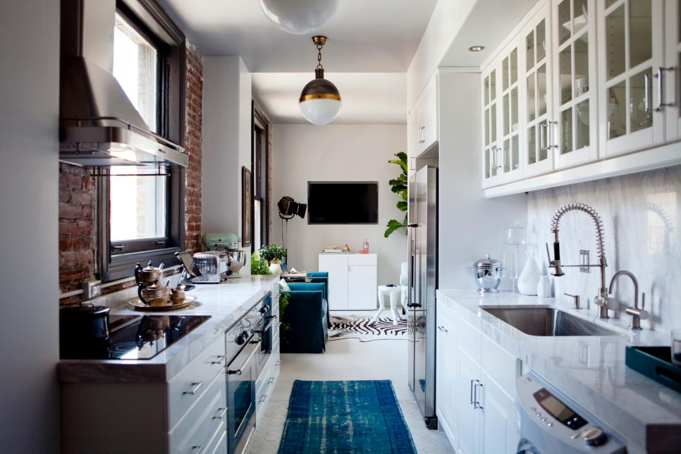 narrow galley kitchen with white lower cabinets and glass door upper cabinets. one wall framing the window has an exposed brick backsplash. a turquoise blue runner rug distracts the eye and adds a touch of style