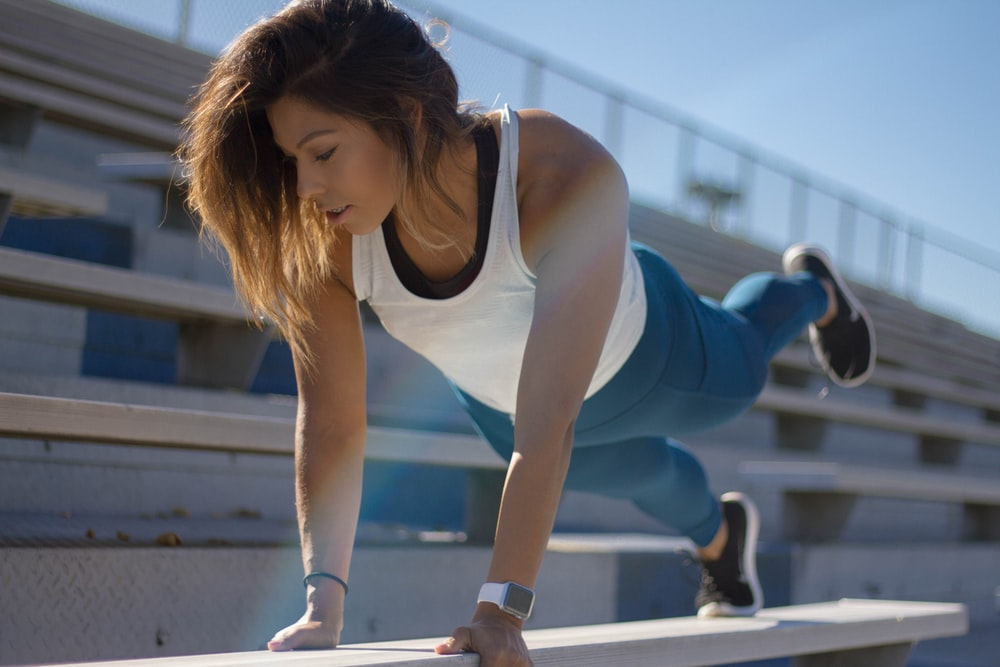 selective focus photography of woman doing planking on bench