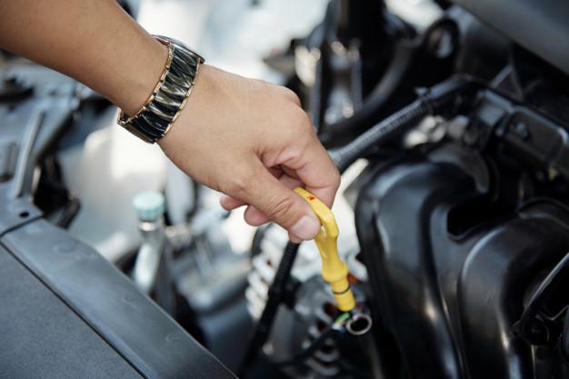 Mão de mecânico conferir o óleo do motor do automóvel
