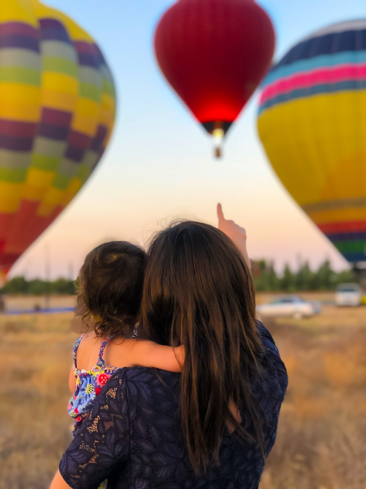 Mother and her little child looking up at the sky towards hot air ballons.