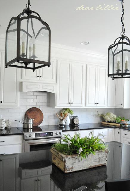 farmhouse black and white kitchen with white raised panel cabinets, glossy black countertops, black pendant lights and a white brick backsplash