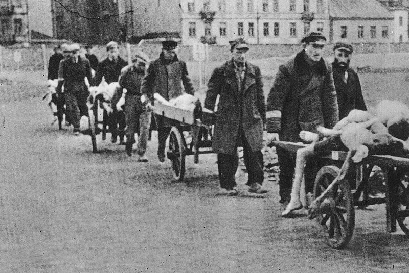 Photograph of men pushing wheelbarrows full of corpses in the Warsaw ghetto.