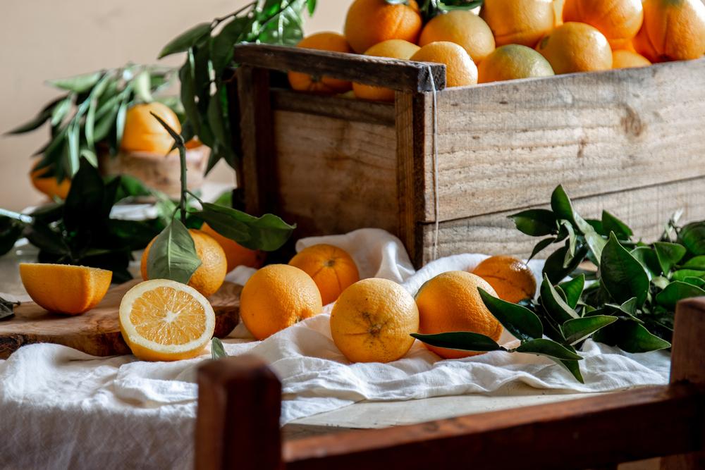 Laranjas dispostas numa mesa, com galho e uma cortada ao meio