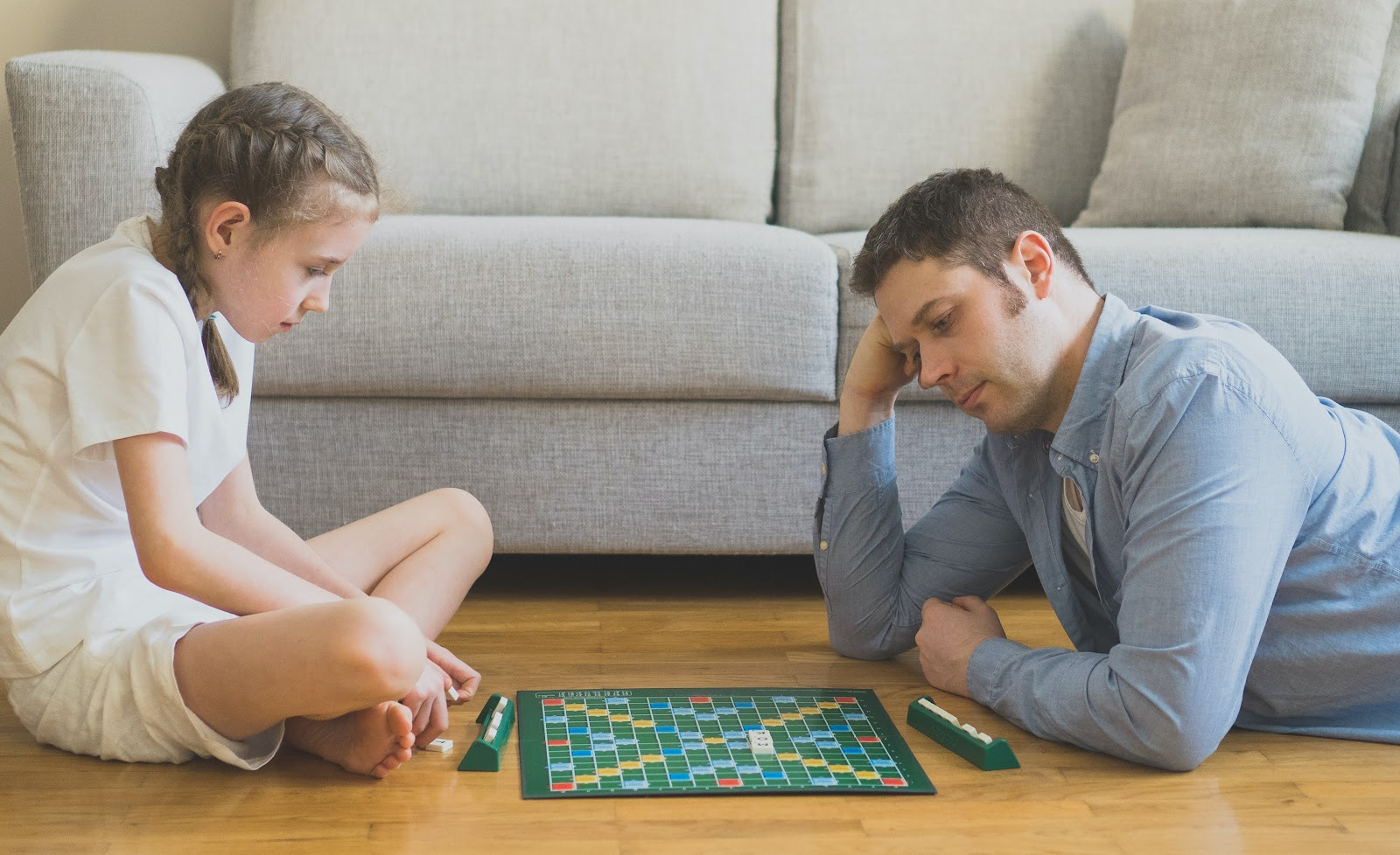 A father and daughter play scrabble on the floor.